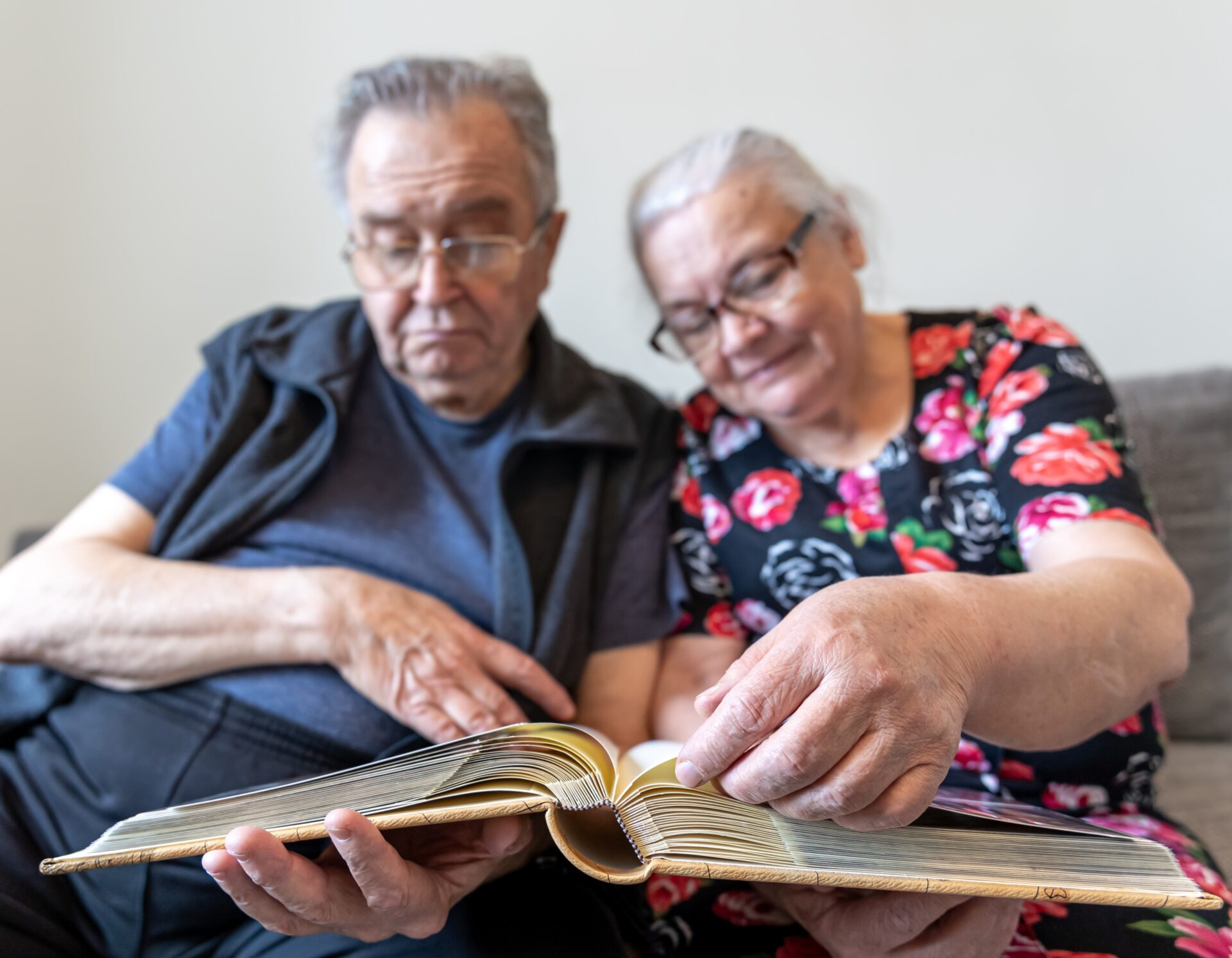 Elderly couple reviewing picture book of past memories