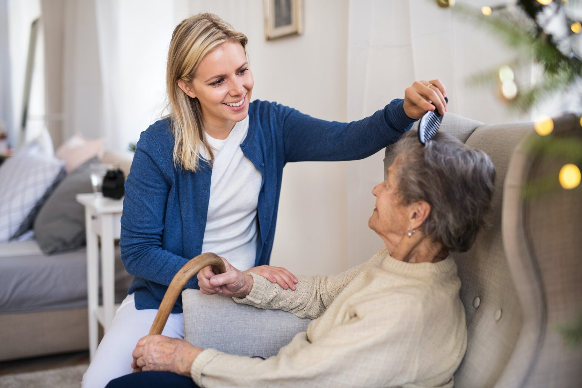 A health visitor combing hair of senior woman at home at Christmas time.