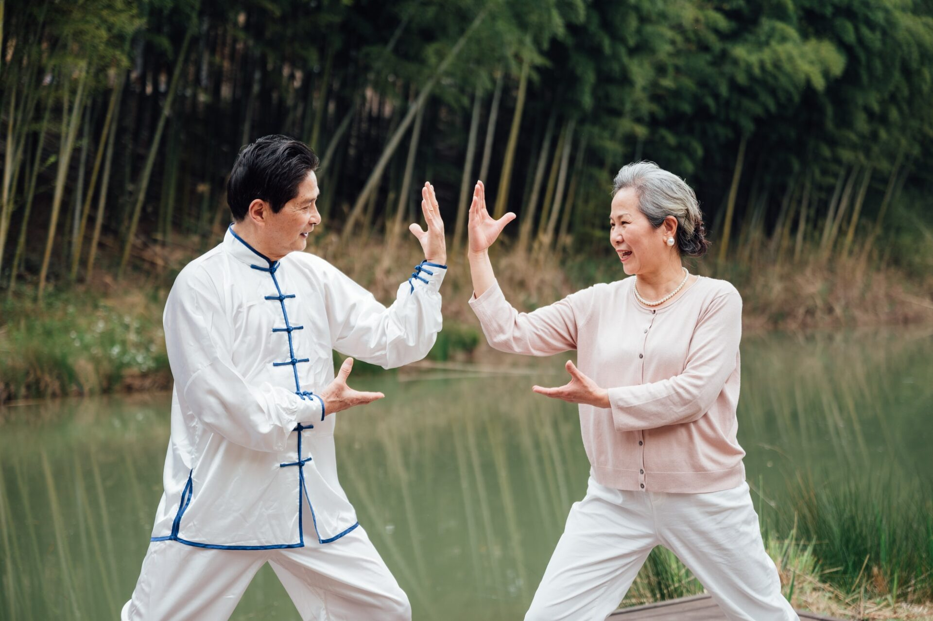 Asian senior couple practicing tai chi outside by the river