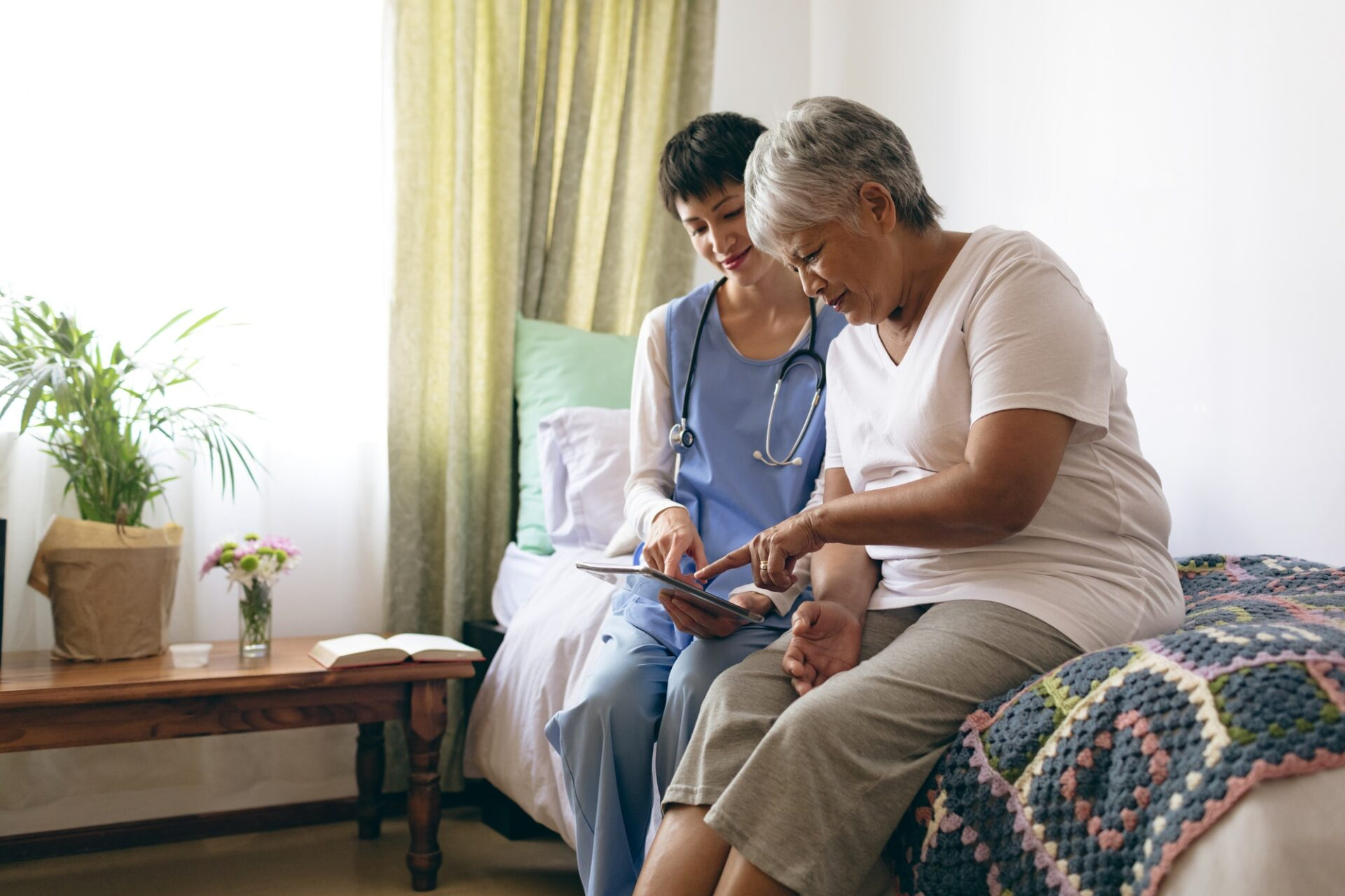 Beautiful female doctor and senior female patient using digital tablet at retirement home
