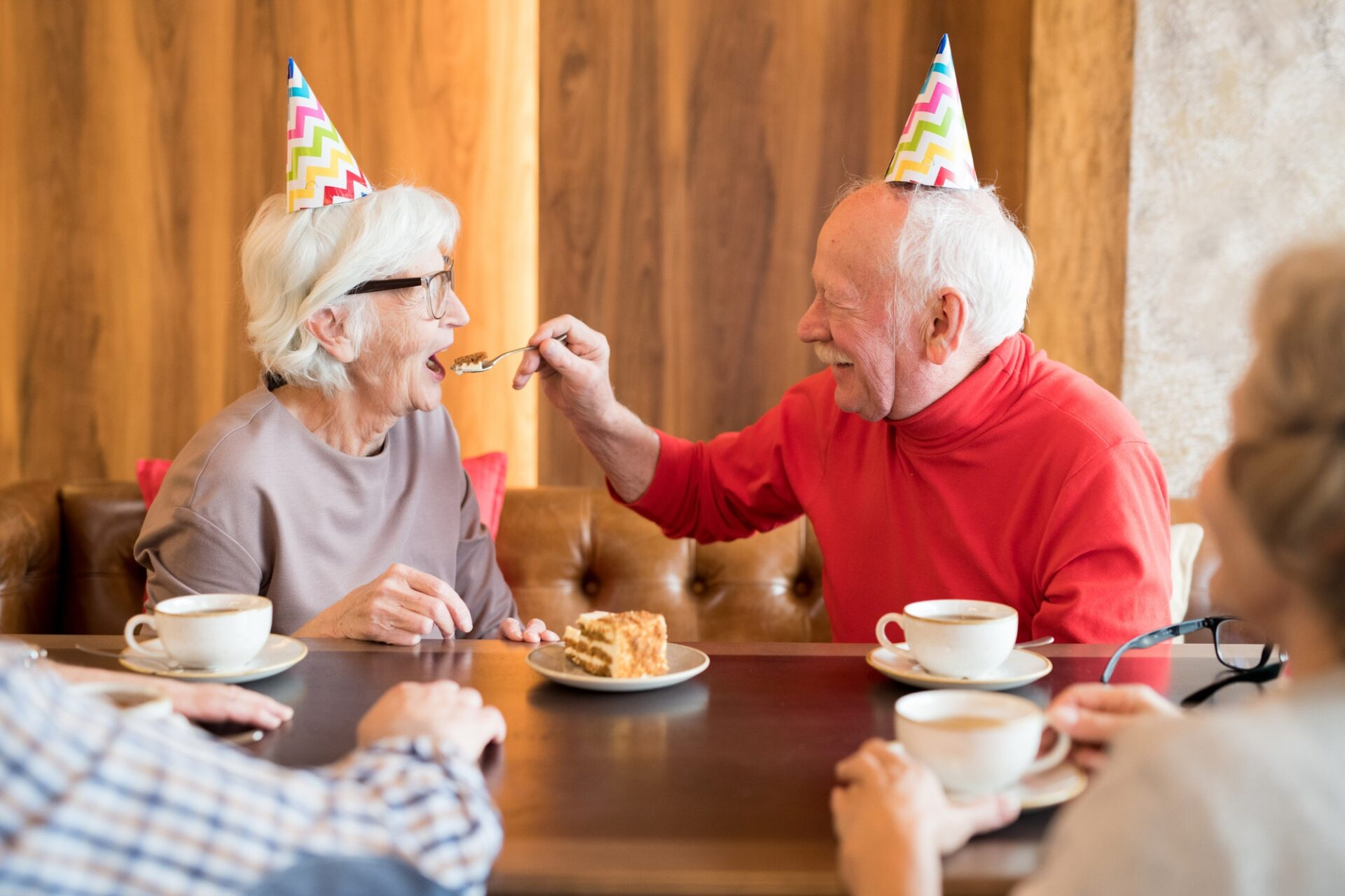 Careful senior husband feeding birthday wife