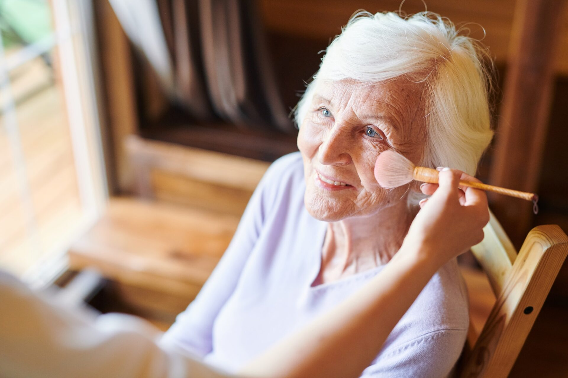 Happy senior female with short white hair looking at beautician