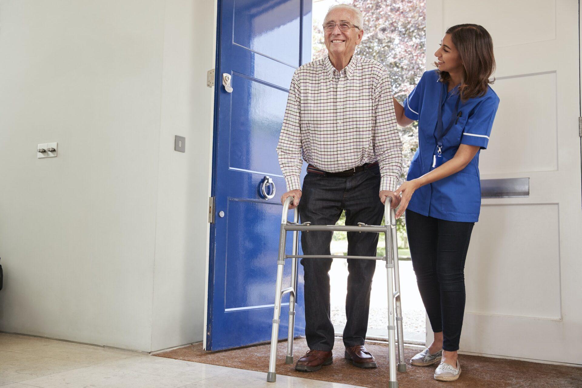 Nurse helping senior man using a walking frame at home