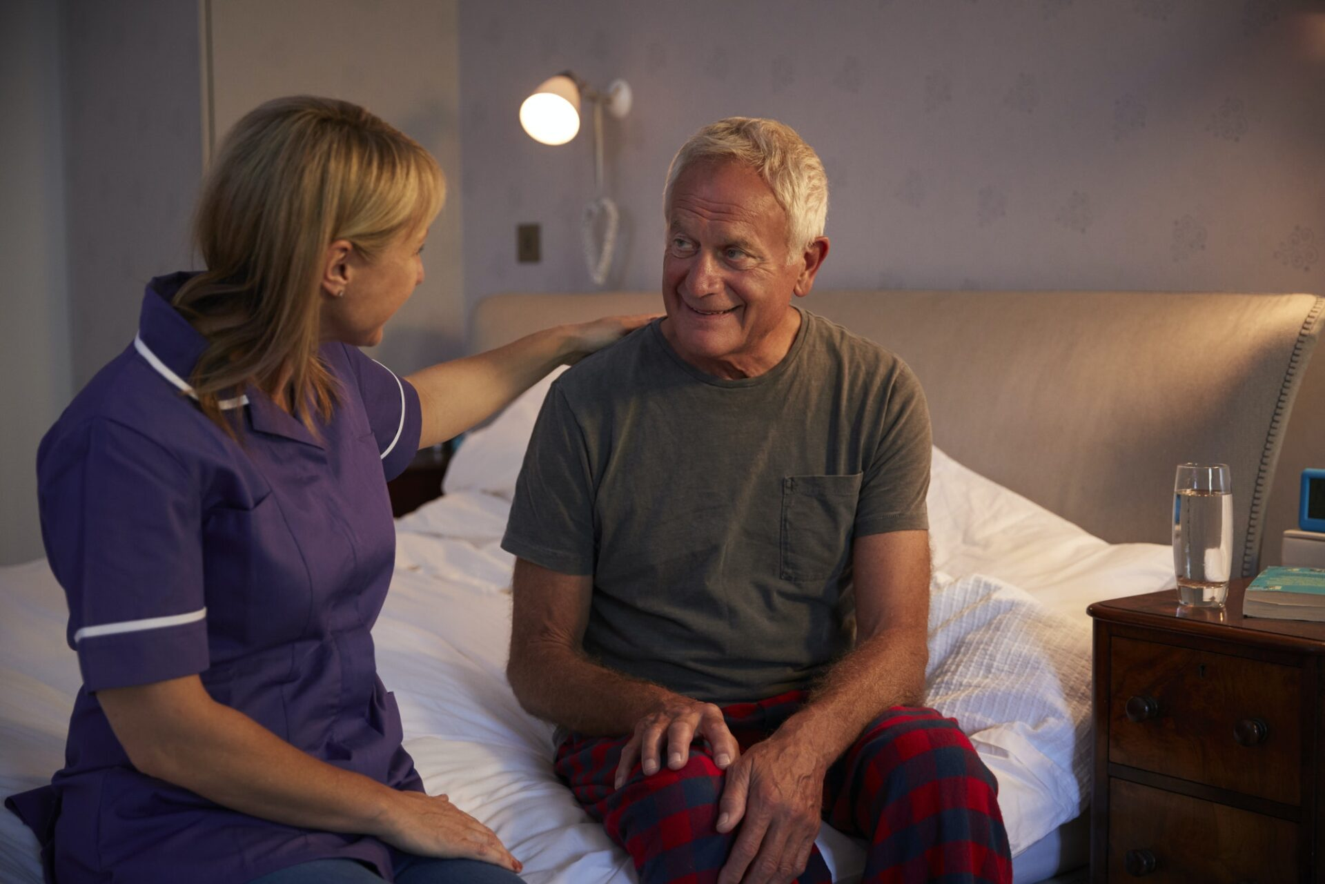 Nurse Talking With Senior Man In Bedroom On Home Visit