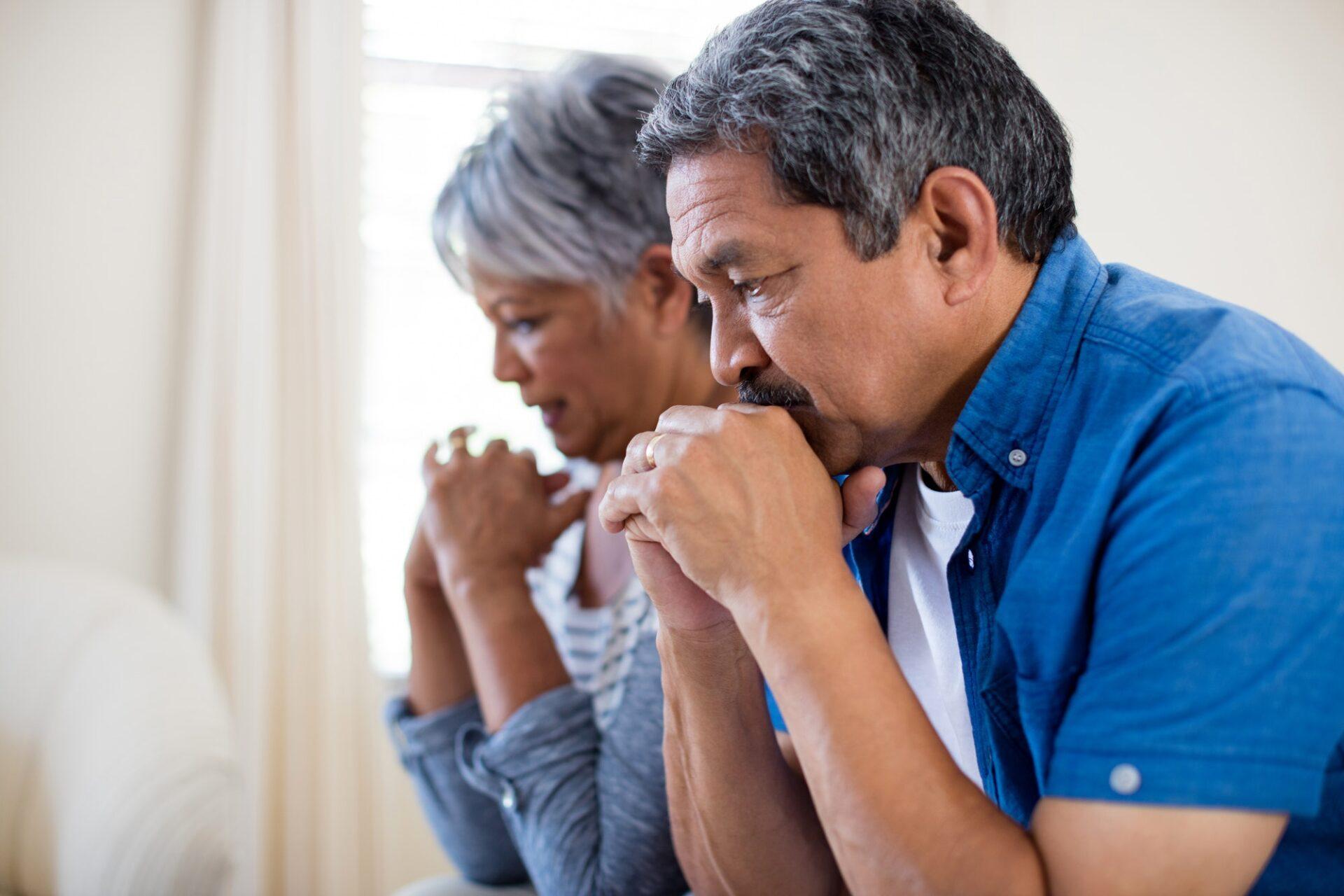 Tensed senior couple in living room