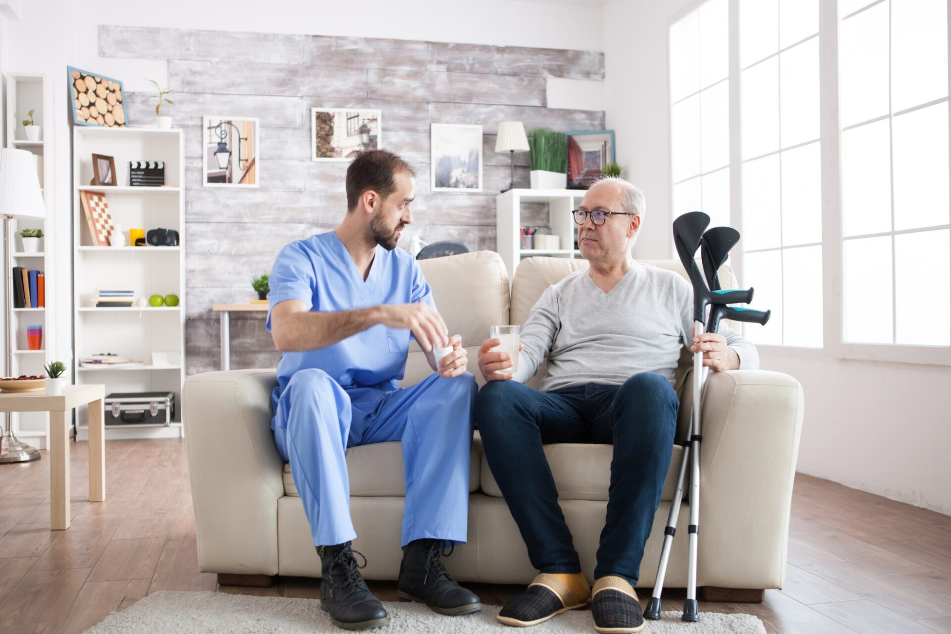 Young male nurse in nursing home with pills for senior man